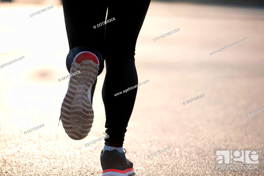 Stock Photo: sporty woman running on sidewalk at early morning jogging with city sunrise scene in background.