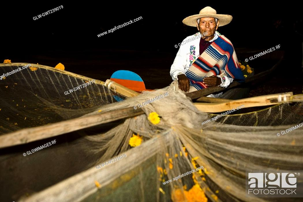 Stock Photo: Portrait of a senior man with butterfly fishing net at night.