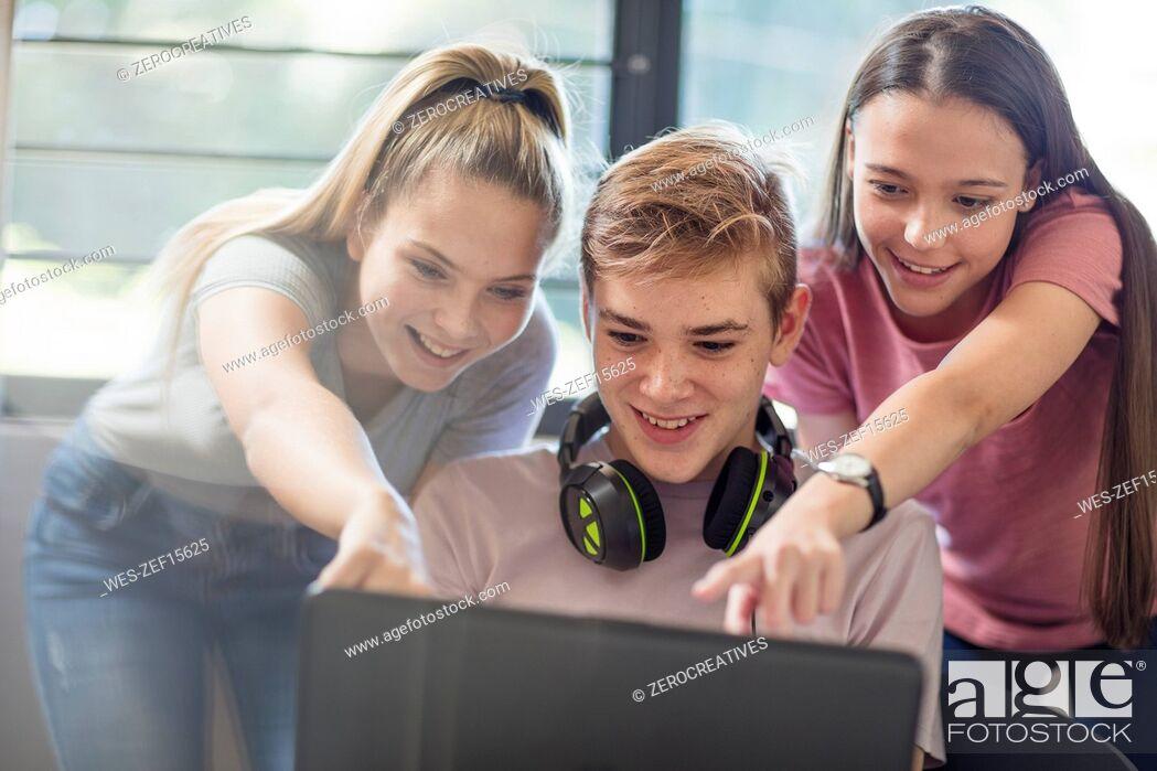 Photo de stock: Teenage girls watching boy using laptop.