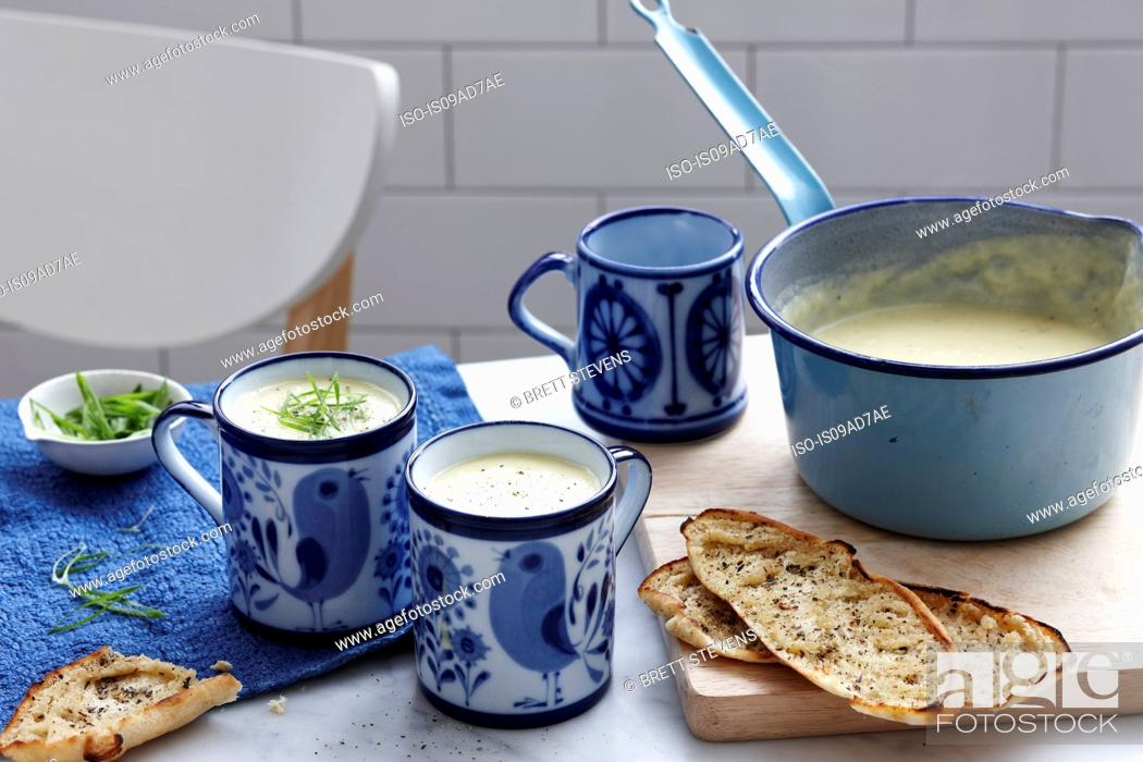 Stock Photo: Meal with mugs of leek and potato soup with bread.