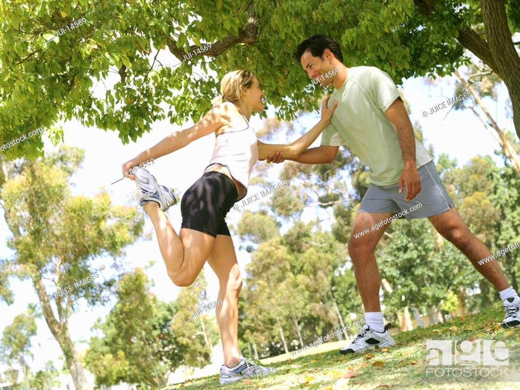 Stock Photo: Young couple stretching in preparation for running, smiling at each other tilt.