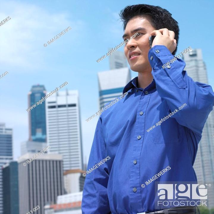 Stock Photo: Low angle view of a businessman talking on a mobile phone.