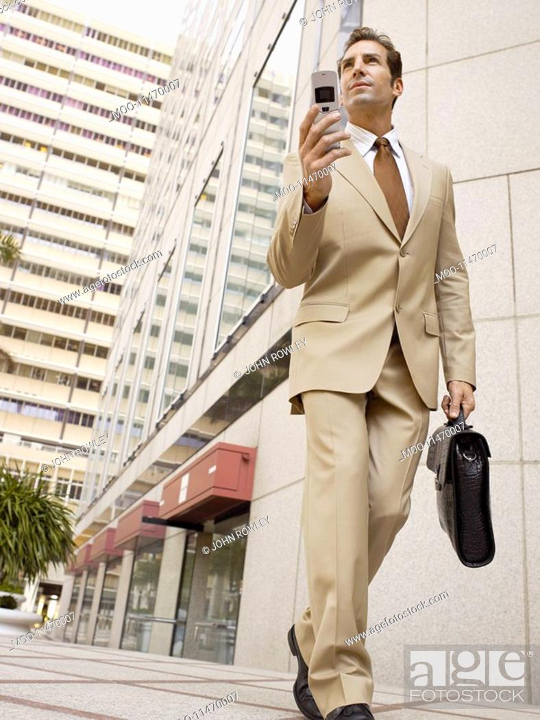 Stock Photo: Businessman using mobile phone outside office building.