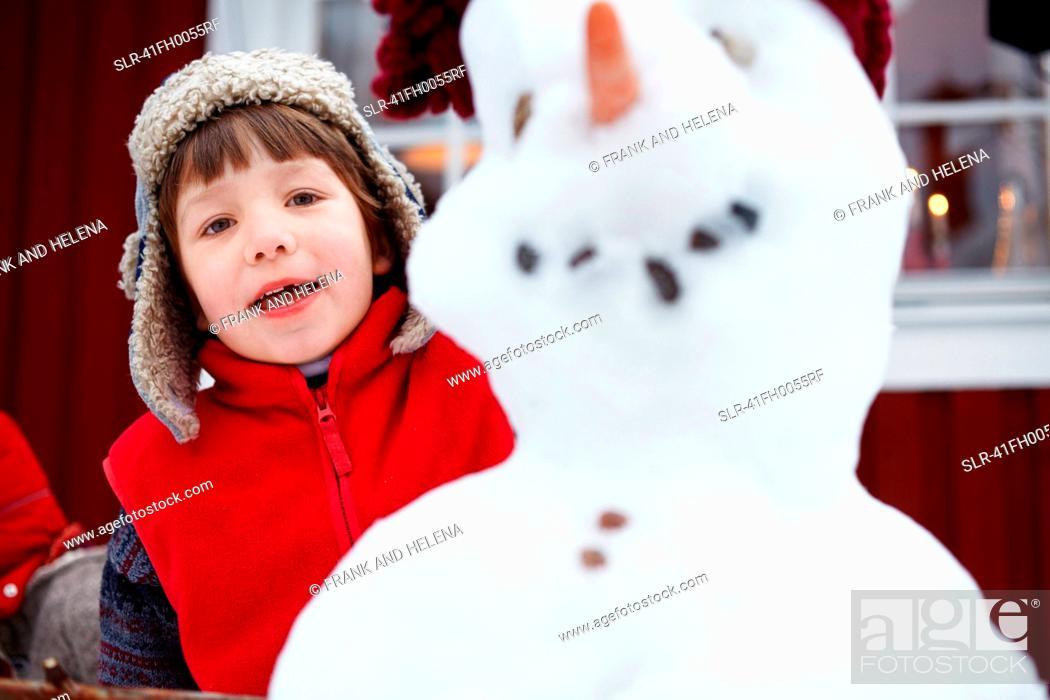 Stock Photo: Boy standing behind snowman.