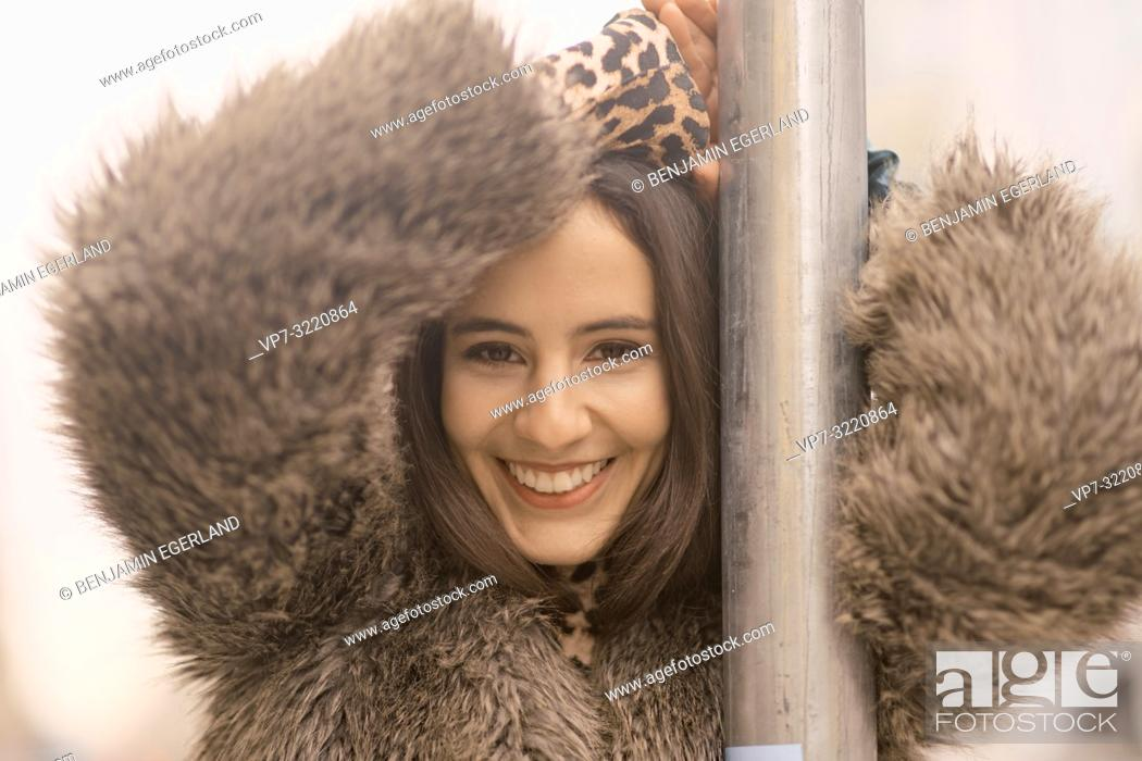 Stock Photo: portrait of young woman in winter coat leaning on traffic sign at street in city, happy smiling, in Munich, Germany.