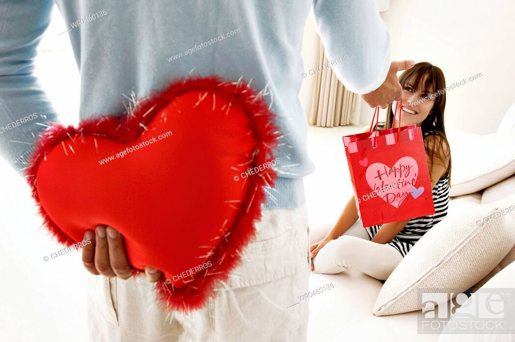 Photo de stock: Mid section view of a man hiding a heart shaped cushion and giving a gift to a young woman.