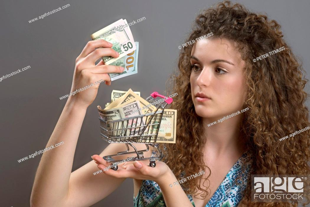 Stock Photo: Concept of the cost of living a woman with serious expression holding supermarket trolley full of cash.