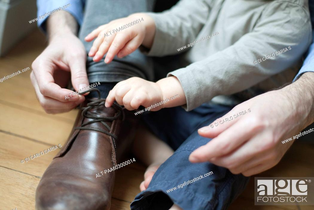 Stock Photo: Chhild helping father tie shoelace.