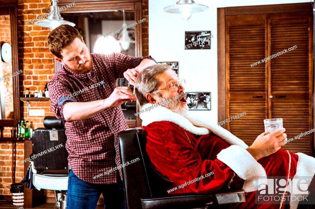 Stock Photo: The senior man in Santa claus costume shaving his personal master at barber shop before Christmas.