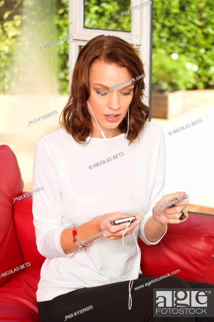 Stock Photo: Young woman using iPhone, holding credit card.