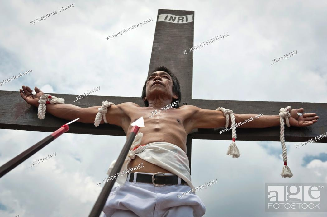 Stock Photo: Alex nailed on the cross during the traditional crucifixions, Good Friday, San Fernando, Pampanga, Philippines.