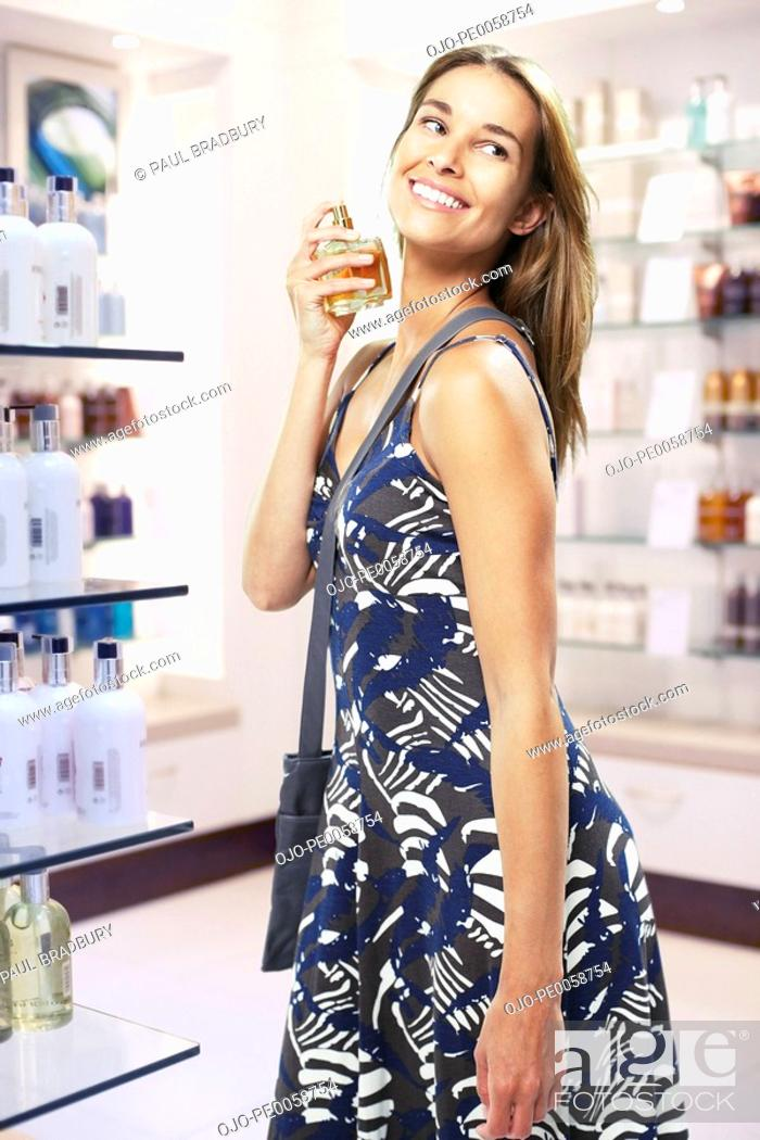 Stock Photo: Woman spraying perfume on herself in store.
