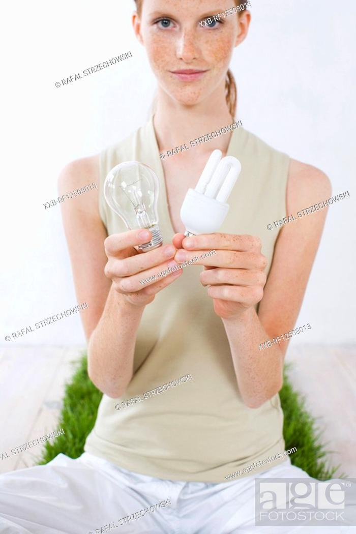 Stock Photo: young woman holding two types of light bulbs.