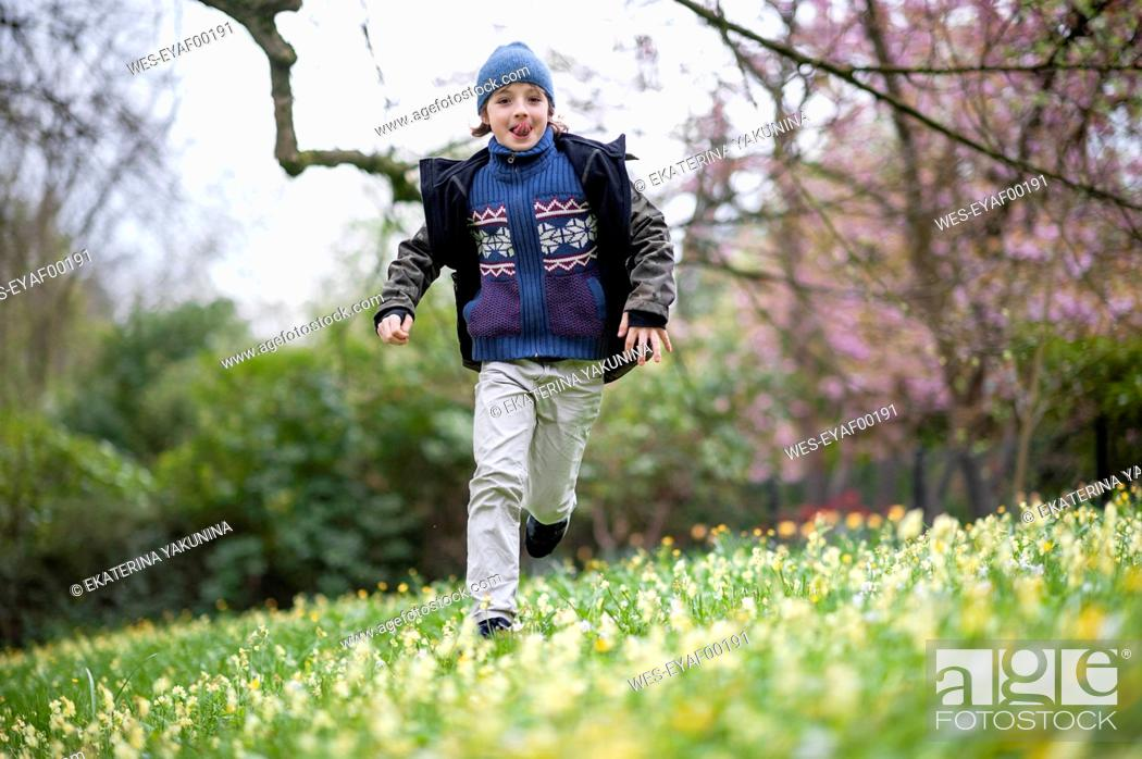 Stock Photo: Portrait of boy running on flower meadow sticking out tongue.