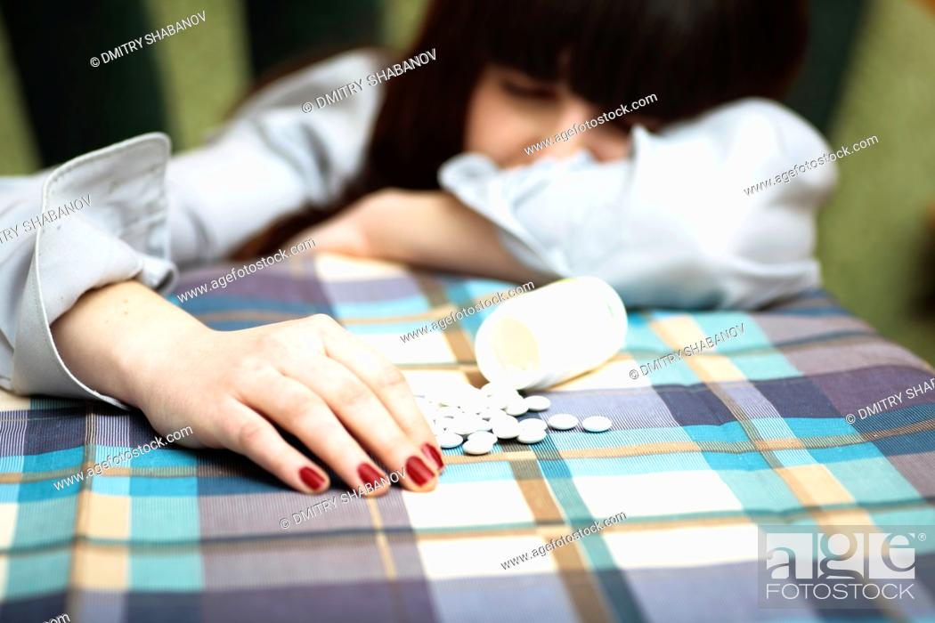 Stock Photo: depression - women and drags open pack of pills on the table.
