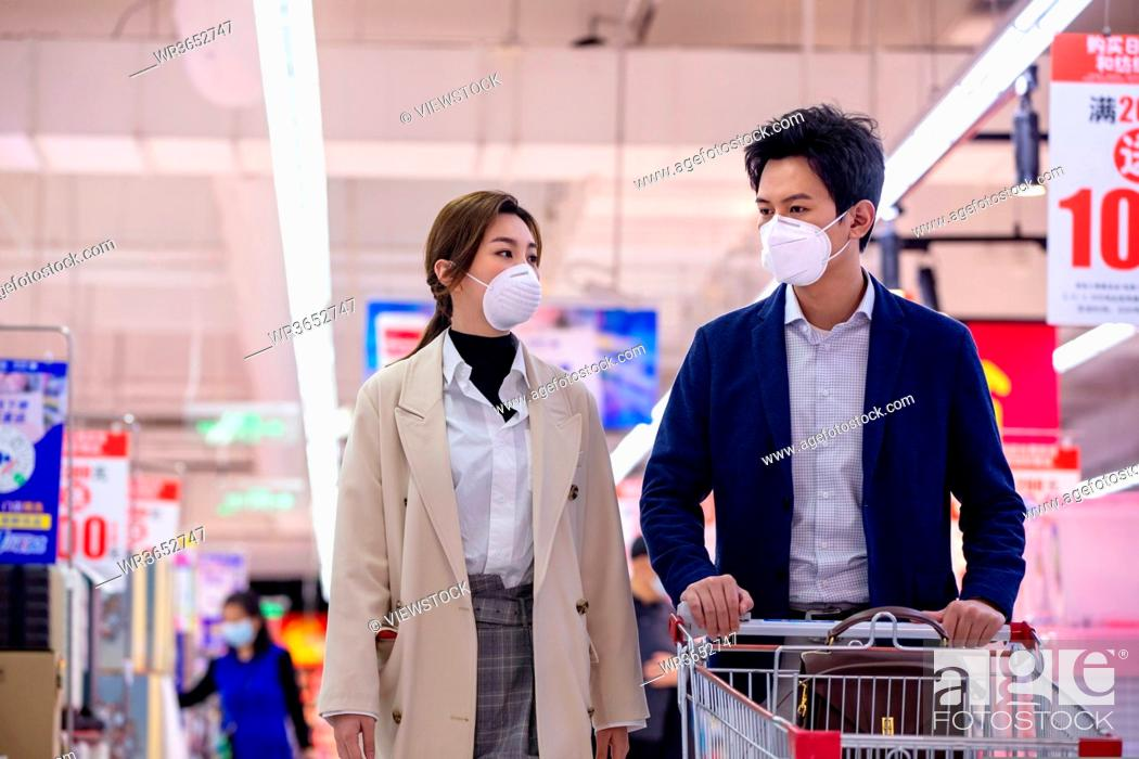 Stock Photo: Wearing a mask of the young couple shopping in the supermarket.