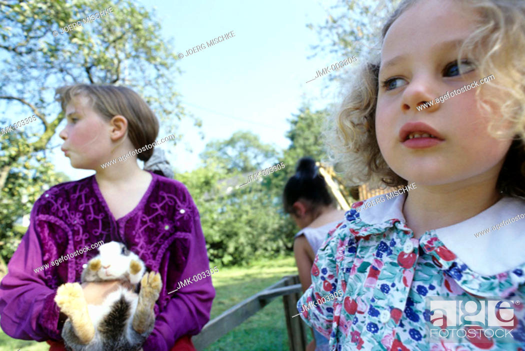 Stock Photo: Three girls, 1-5 5-10 years old, playing with rabbits, bunnies, in the garden in summer.