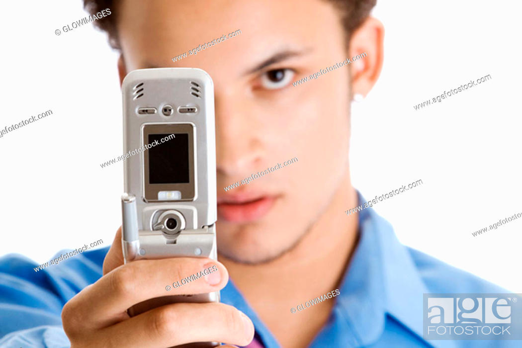 Stock Photo: Close-up of a young man taking a photograph of himself with a mobile phone.