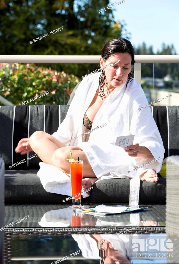 Imagen: A mature woman relaxes at the outdoor patio with a cocktail while visiting the Kingfisher Resort and spa. Courtenay, Vancouver Island, british Columbia, Canada.