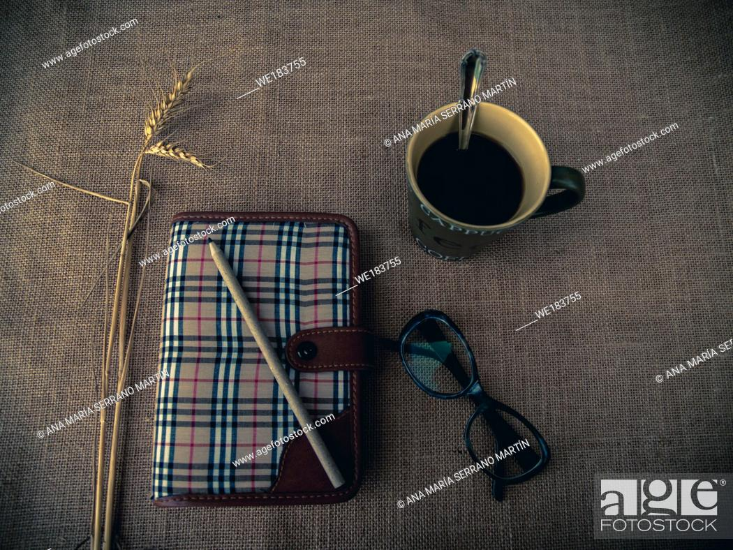 Stock Photo: Vintage style. Organized desk with closed diary, eye glasses, a cup of coffee, dry grass, pencil and burlap background.