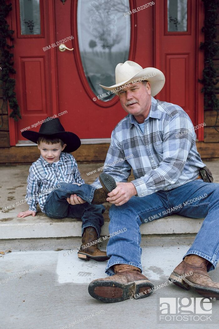 Stock Photo: Caucasian farmer and grandson sitting on front porch.