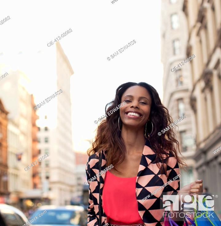 Stock Photo: Smiling woman walking on city street.