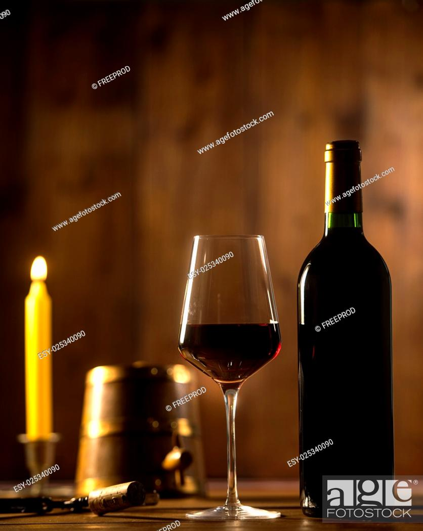 Imagen: Pouring red wine into wineglass from green bottle, brown background.