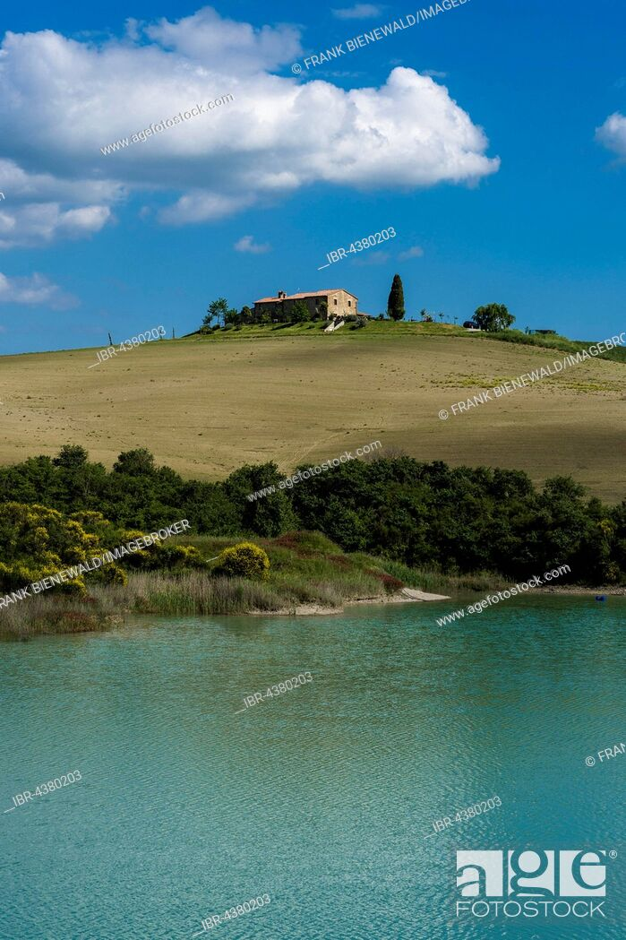 Stock Photo: Typical green Tuscan landscape in Val d'Orcia, farm on hill, lake and blue cloudy sky, La Foce, Tuscany, Italy.