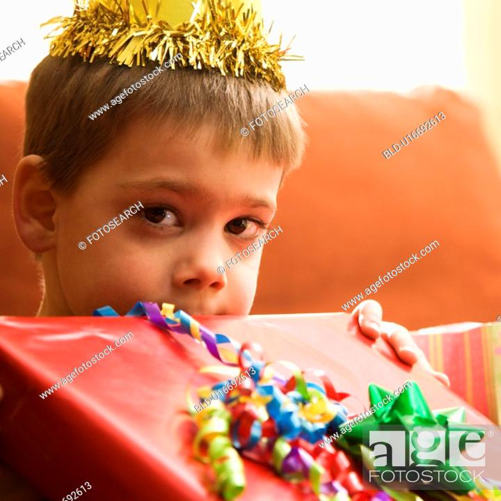 Stock Photo: Boy holding gift up to face.