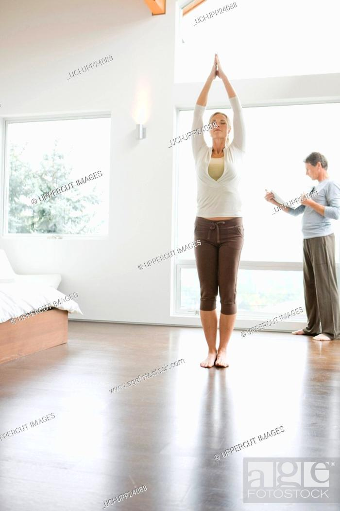 Stock Photo: Woman standing in yoga pose and man reading newspaper.