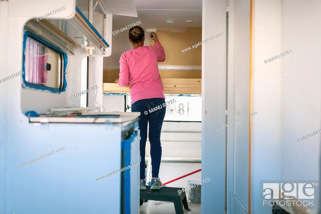 Stock Photo: Young blonde woman painting and restoring caravan.