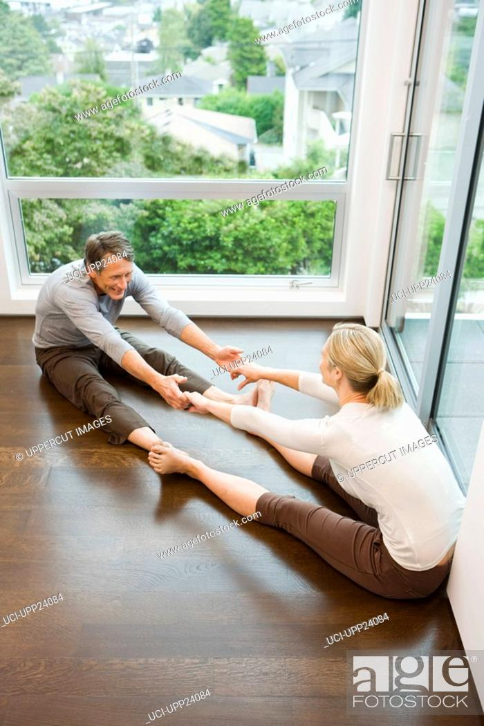Stock Photo: Couple stretching with feet and hands touching.