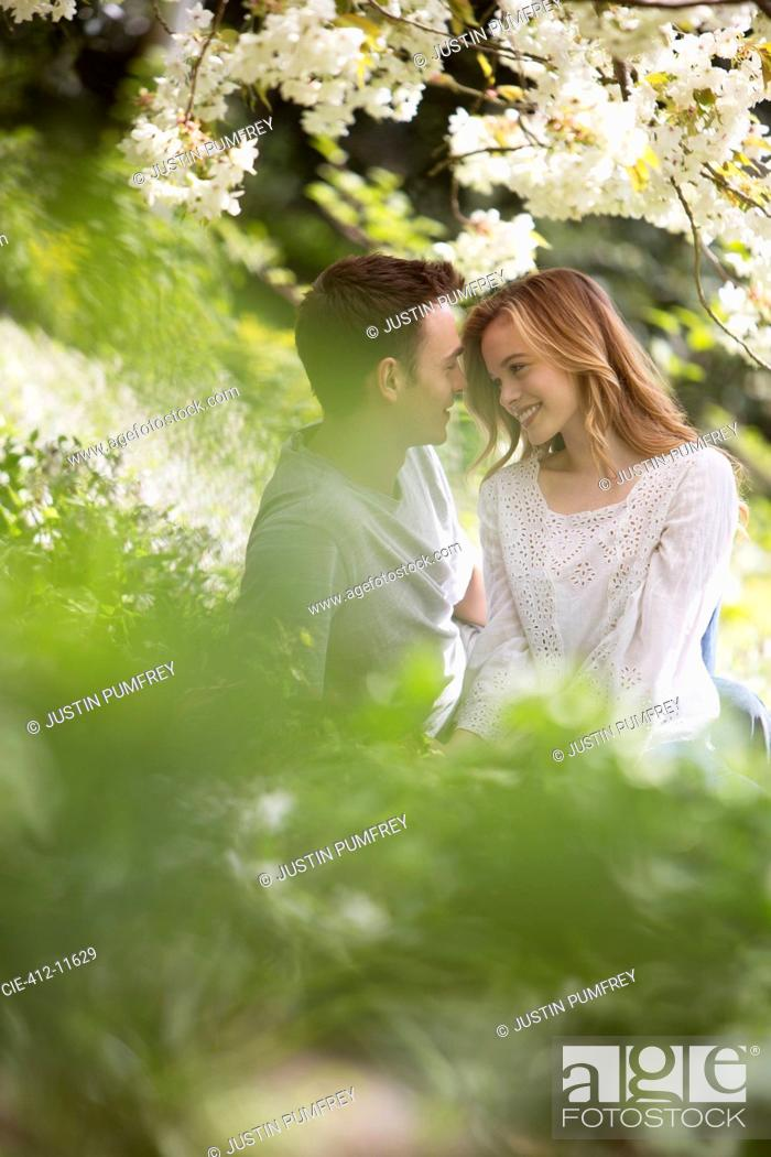 Stock Photo: Couple relaxing in grass outdoors.