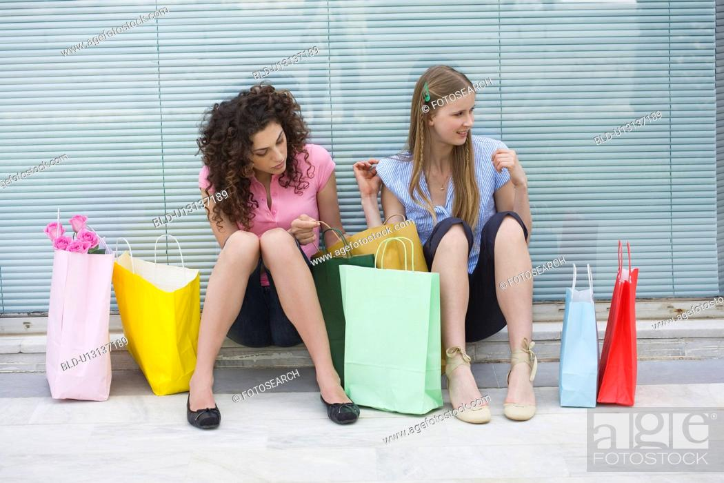 Stock Photo: Two women sitting with shopping bags.