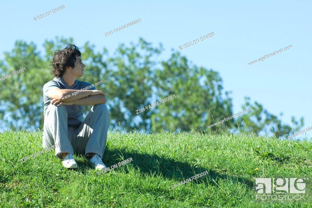 Stock Photo: Teen boy sitting on grassy hill, relaxing.