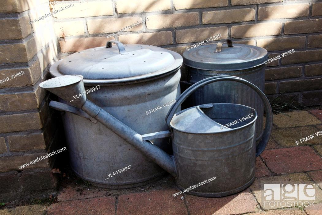 Stock Photo: Still life of watering can and to vats in the garden. The Netherlands.