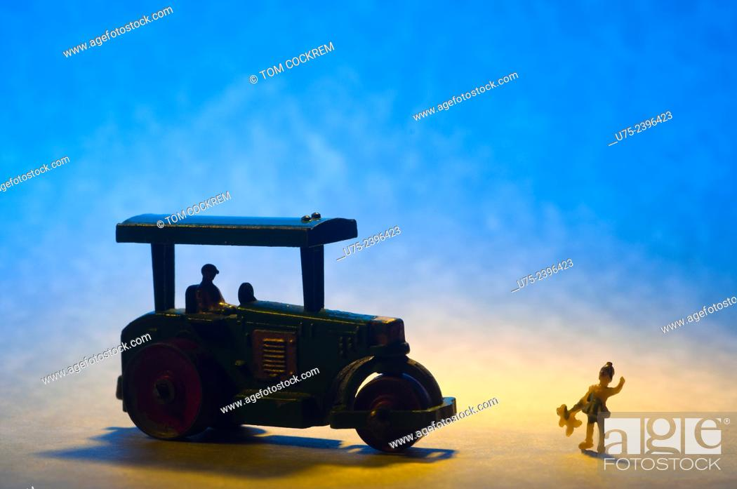 Stock Photo: Miniature toy steamroller with mini figure of girl in studio setting.