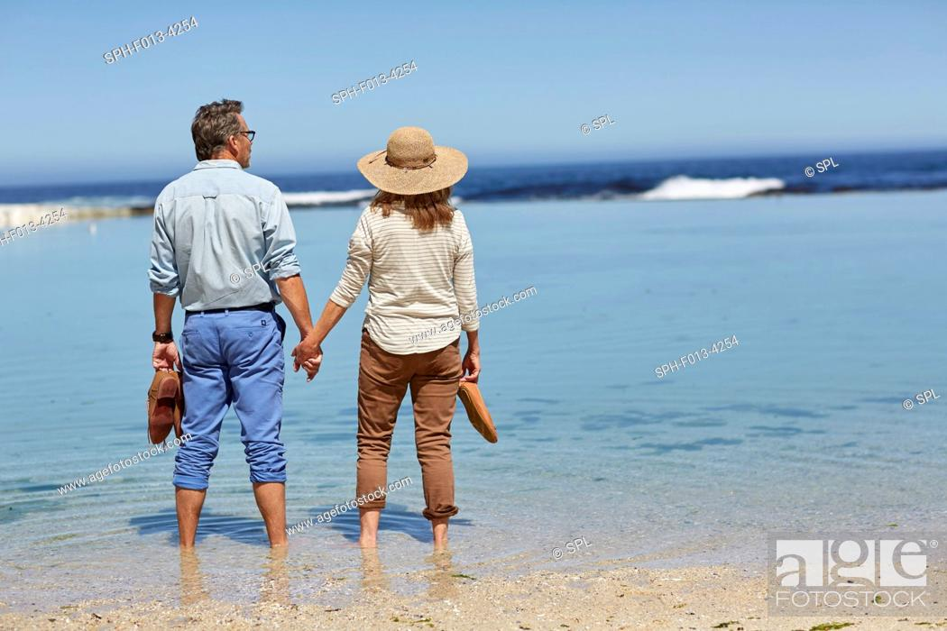 Stock Photo: MODEL RELEASED. Senior couple holding hands, paddling in the sea.