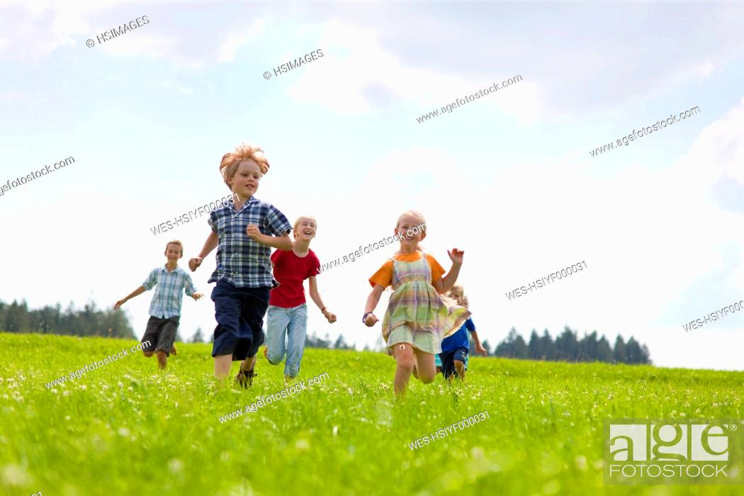 Stock Photo: Germany, Bavaria, Group of children running through meadow.