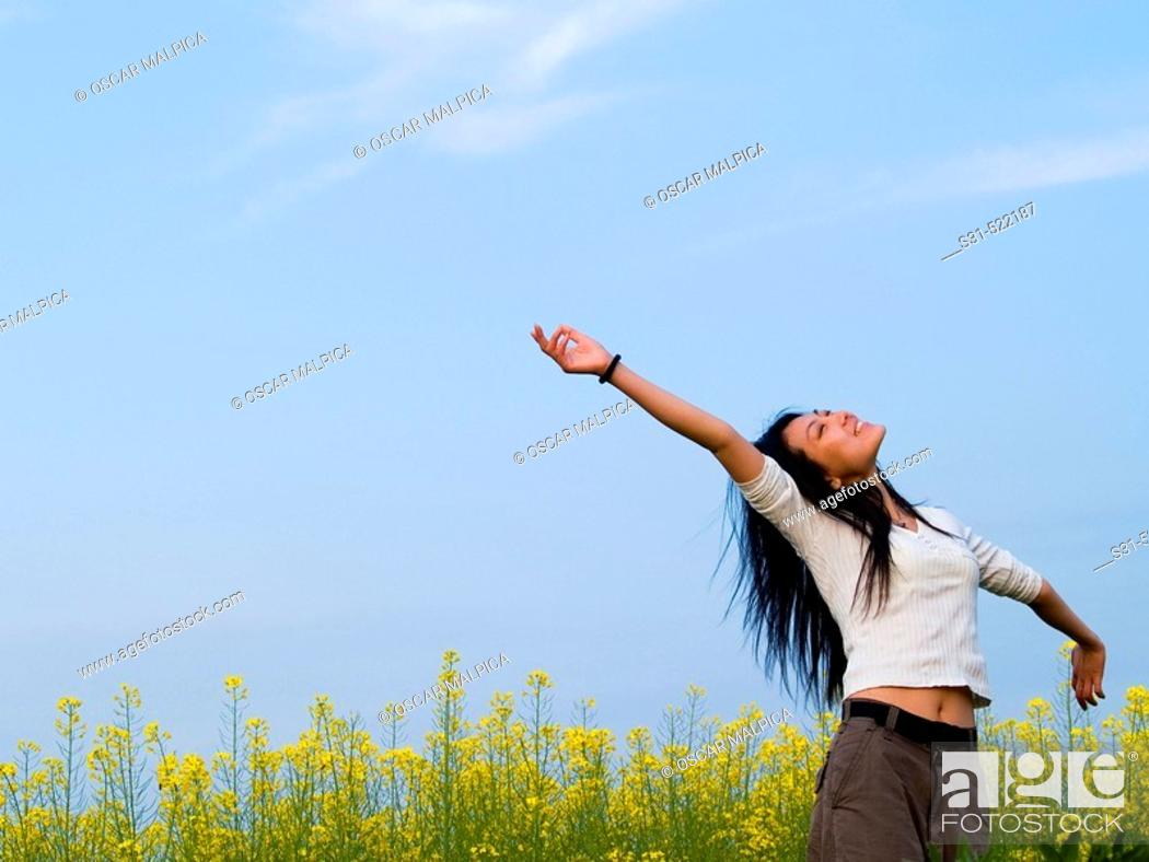 Stock Photo: Young good looking asian (chinese) girl enjoying the outdoors in a rape field.