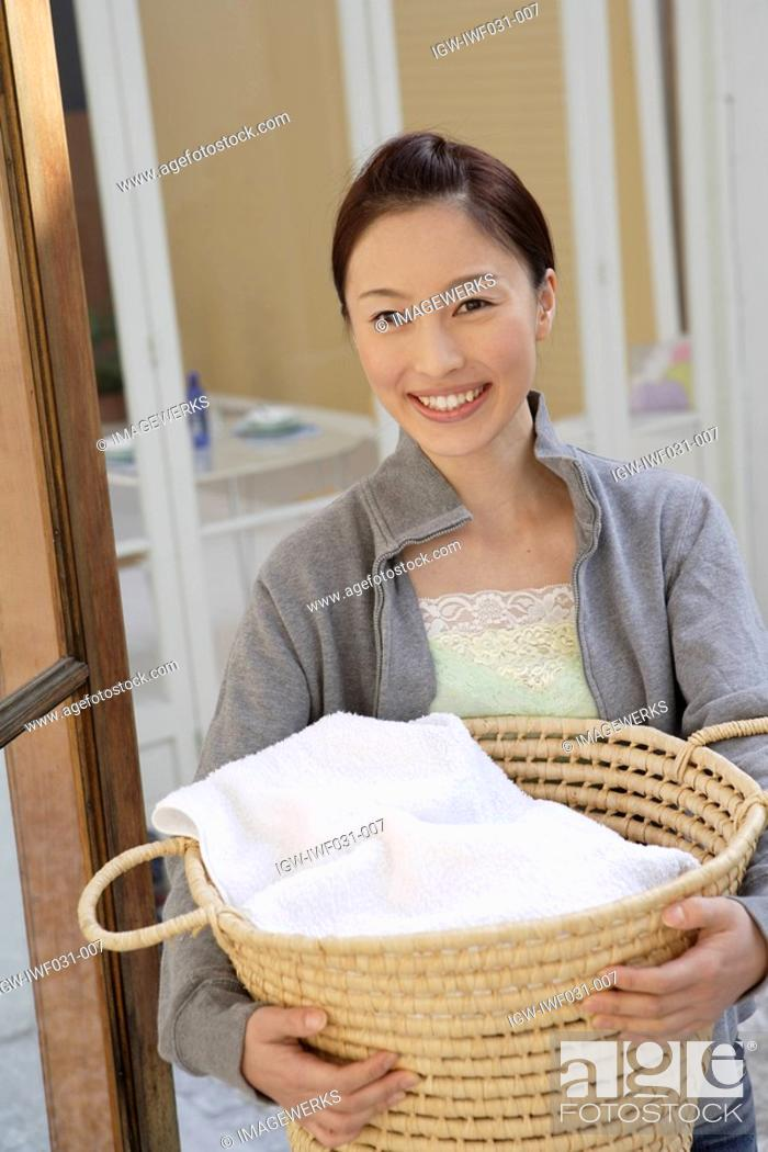 Stock Photo: Portrait of a young woman holding a basket.