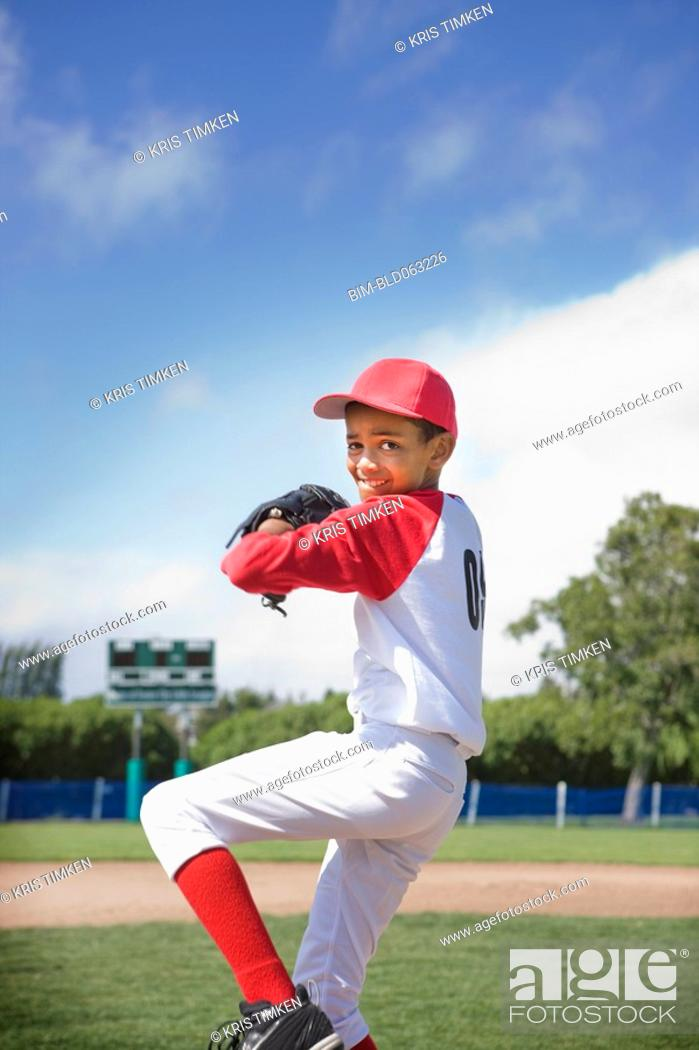 Stock Photo: Mixed race boy pitching in baseball game.