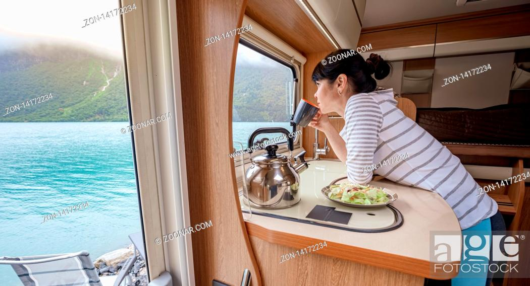 Stock Photo: Woman in the interior of a camper RV motorhome with a cup of coffee looking at nature.