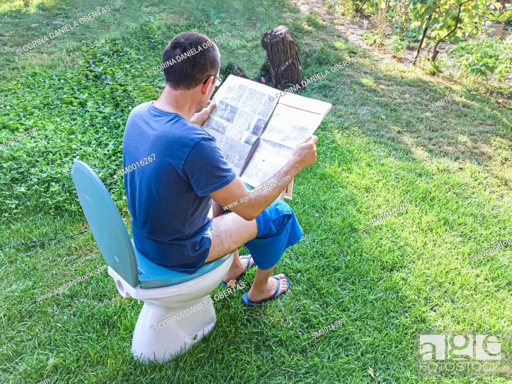 Stock Photo: Funny quarantine moments - Man sitting on a toilet chair and reading newspaper outside in his garden.