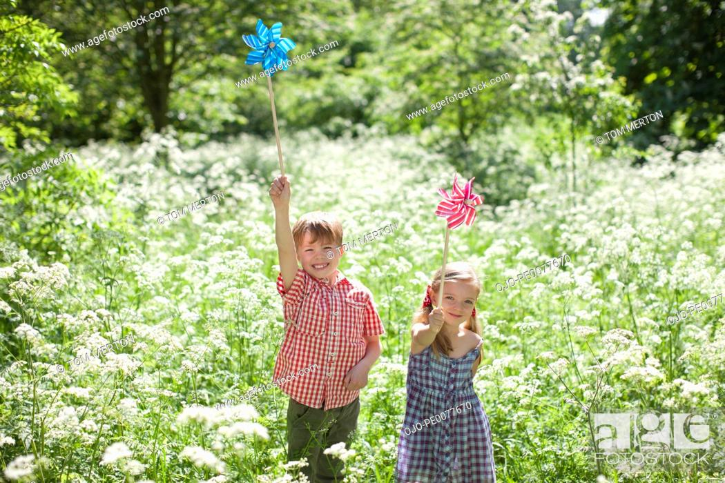 Stock Photo: Children playing with pinwheels in field of flowers.