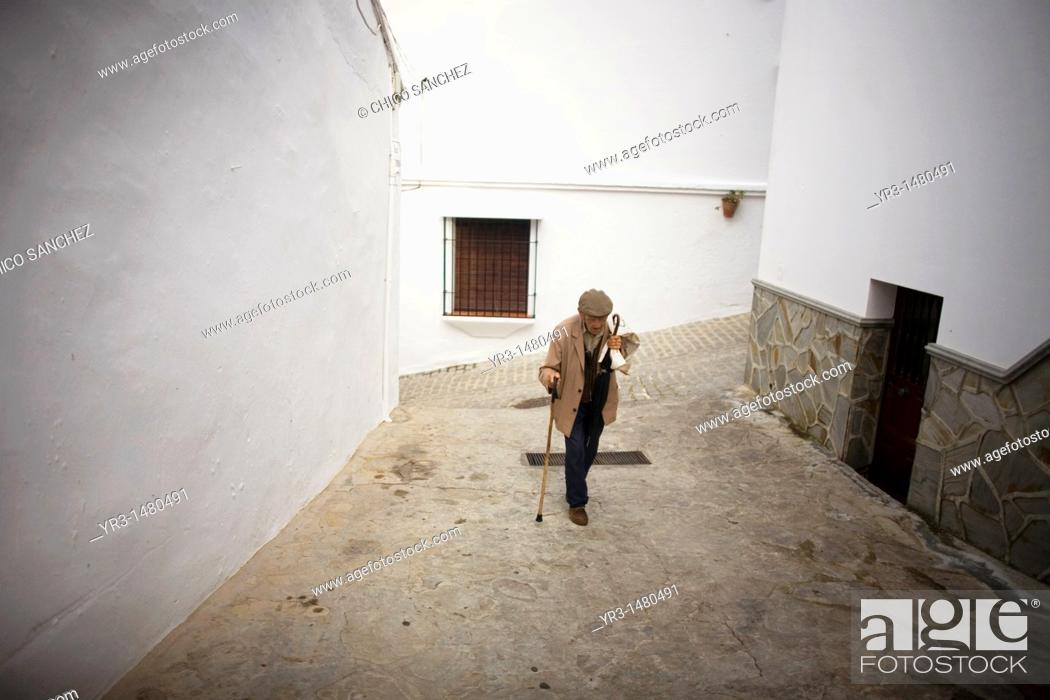 Stock Photo: A senior man ups a hill using his walking stick in a street of El Gastor village in the Sierra de Grazalema Natural Park, Cadiz province, Andalusia, Spain.