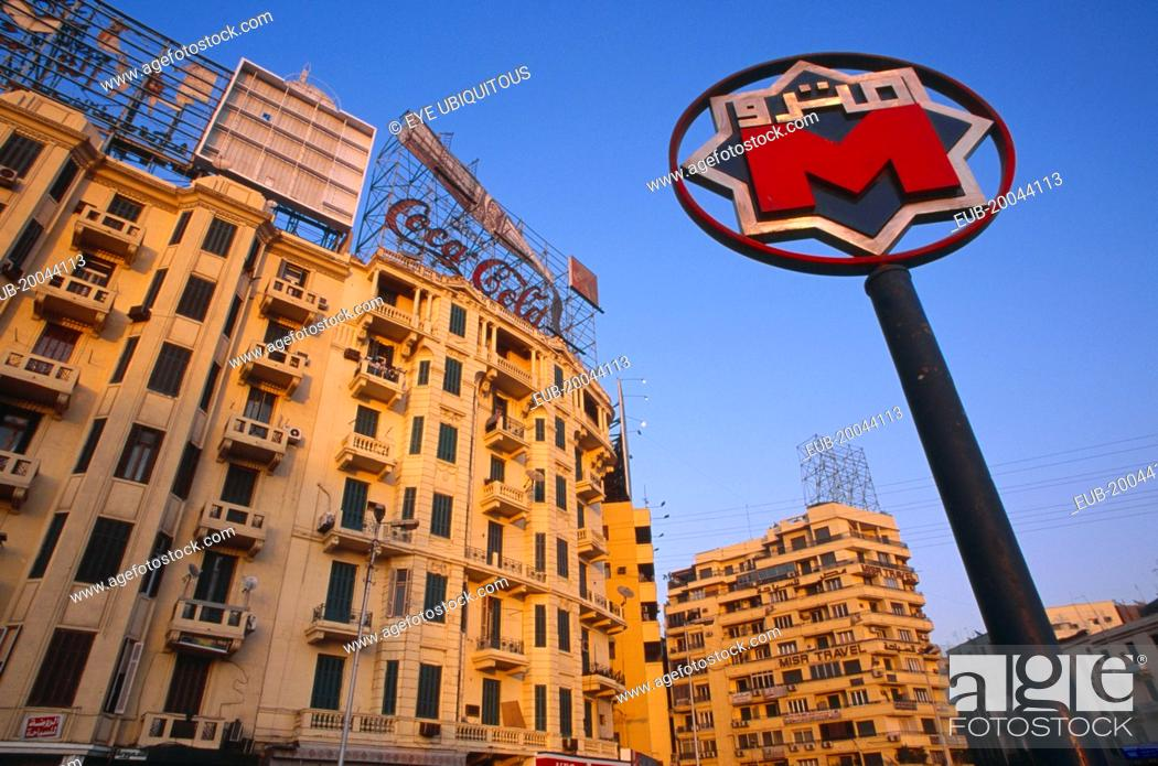 Stock Photo: Sadat metro station sign on Midan Tahrir with city buildings and advertising for Coca Cola and Kentucky Fried Chicken behind.