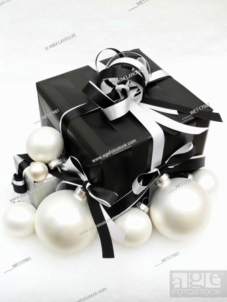 Stock Photo: Christmas gift with baubles on snowy background, vintage toned.