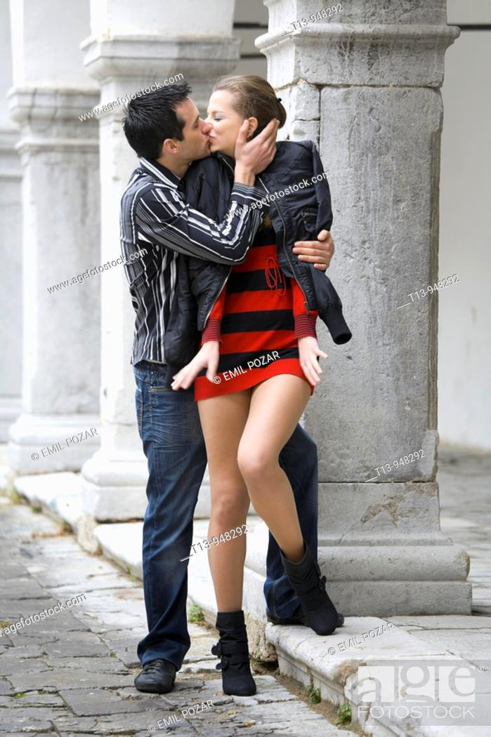 Stock Photo: Young couple kissing on romantic street.
