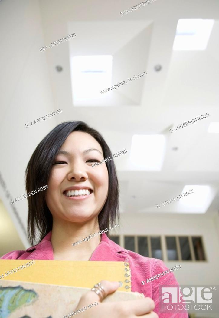 Stock Photo: Female Asian teenager holding notebooks.
